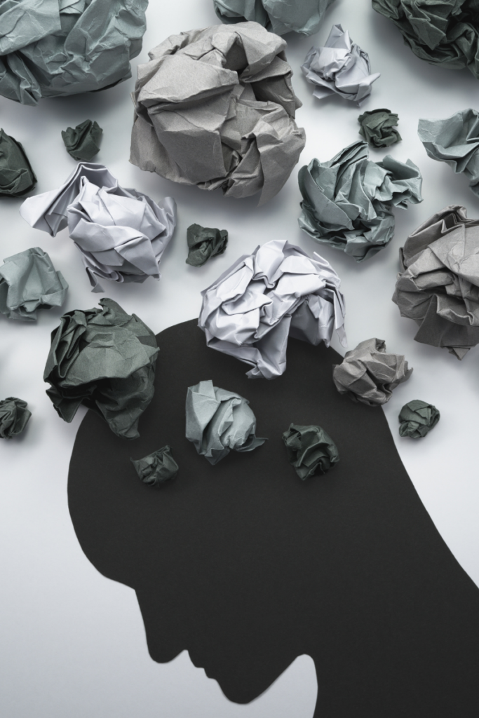 Shadow of a head with lumps of paper, depicting thoughts.